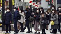 Orang-orang yang mengenakan masker menunggu lampu lalu lintas di penyeberangan pejalan kaki di Shibuya, Tokyo, Jepang, Selasa (5/1/2021). Ibu kota Jepang, Tokyo mengonfirmasi lebih dari 1.200 kasus virus corona COVID-19 baru pada Selasa (5/1). (AP Photo/Eugene Hoshiko)