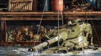 Aktivis lingkungan menenggelamkan sebuah tank lama ke dasar Laut Mediterania di lepas pantai kota pelabuhan Sidon, Lebanon, Sabtu (28/7). Mereka menenggelamkan 10 tank lama yang disediakan oleh Angkatan Bersenjata Lebanon. (AFP / Mahmoud ZAYYAT)