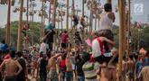 Warga mengikuti lomba Panjat Pinang Kolosal dalam rangka merayakan HUT ke-74 Kemerdekaan RI di Pantai Karnaval Ancol, Jakarta, Senin (17/8/2019). Sebanyak 174 batang pinang dengan beragam hadiah disediakan dalam lomba yang diikuti ratusan warga itu. (Liputan6.com/Faizal Fanani)