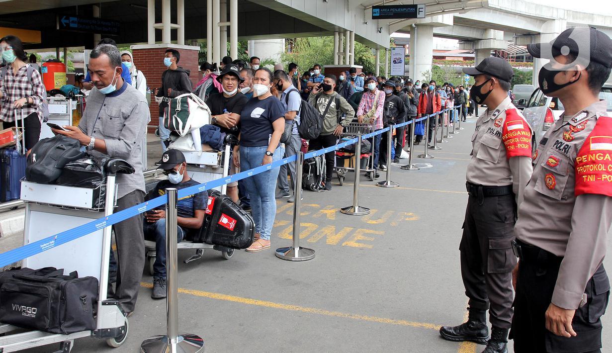 Polisi berjaga saat calon penumpang mengntre untuk rapid test antigen di Terminal 2 Bandara Soekarno-Hatta, Tangerang, Banten, Selasa (22/12/2020). Calon penumpang mengaku rata-rata antre hingga tiga jam untuk mendapatkan layanan rapid test antigen. (merdeka.com/Arie Basuki)