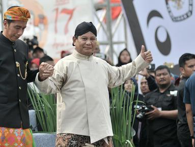 Capres nomor urut 01 dan 02, Joko Widodo (kiri) dan Prabowo Subianto bergandengan tangan saat menuruni panggung Deklarasi Kampanye Damai di Monas, Jakarta, Minggu (23/9). Deklarasi menandai dimulainya masa kampanye Pemilu 2019. (Merdeka.com/Iqbal Nugroho)