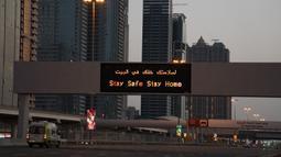 Sebuah ambulans melintasi Jalan Sheikh Zayed 12 yang sepi di Dubai, Uni Emirat Arab, Minggu (5/4/2020). Selama lockdown, warga Dubai dilarang meninggalkan rumah kecuali untuk urusan mendesak dan penting. (AP Photo/Jon Gambrell)