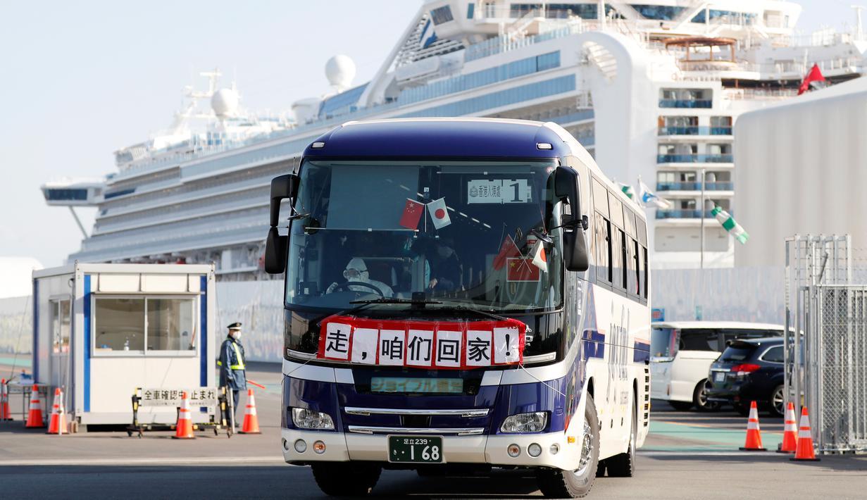 Bus dengan spanduk China bertuliskan 'Pergi, Kita Pulang!' membawa penumpang Hong Kong dari kapal pesiar Diamond Princess yang dikarantina di Yokohama, Jepang, Jumat (21/2/2020). Ratusan orang yang dinyatakan negatif virus corona (COVID-19) berangsur meninggalkan kapal. (AP Photo/Eugene Hoshiko)