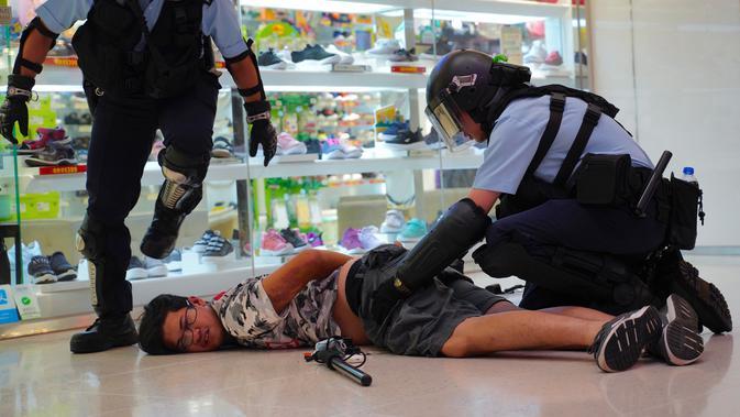 Polisi menahan seorang pria muda setelah perkelahian antara demonstran pro China dengan demonstran antipemerintah di Amoy Plaza, Distrik Kowloon Bay, Hong Kong, Sabtu (14/9/2019). Personel Kepolisian Hong Kong yang bersenjatakan tongkat dikerahkan untuk menangani bentrokan. (AP Photo/Vincent Yu)