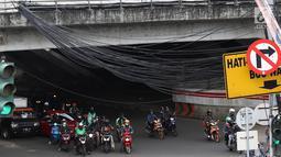Kendaraan melintas di bawah Instalasi kabel menjuntai di Jalan Dewi Sartika, Jakarta Timur, Sabtu (19/1). Selain mengganggu keindahan kota, kondisi tersebut juga berbahaya karena dapat memicu hubungan pendek arus listrik. (Liputan6.com/Immanuel Antonius)