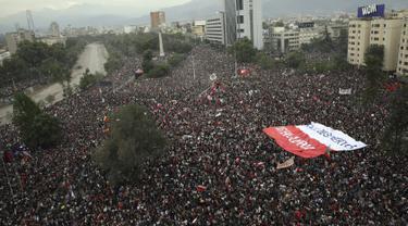 Warga berkumpul saat protes antipemerintah di Santiago, Chile, Jumat (25/10/2019). Sekitar satu juga warga Chile turun ke jalan menuntut Presiden Sebastian Pinera mundur dari jabatannya. (AP Photo/Rodrigo Abd)