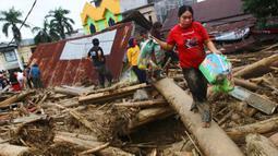 Orang-orang berjalan di atas puing-puing di daerah yang terkena banjir bandang di Masamba, Sulawesi Selatan, Rabu (15/7/2020). Banjir bandang yang terjadi akibat tingginya curah hujan itu mengakibatkan 16 orang meninggal dunia, sementara ratusan rumah rusak berat dan hilang. (AP/Khaizuran Muchtamir)