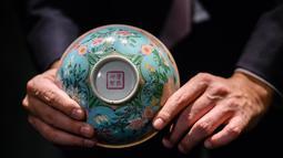 Tampak bawah mangkuk Dinasti Qing saat dipamerkan di Rumah Lelang Sotheby's di Hong Kong, Kamis (2/3). Mangkuk berdiameter 14,7 centimeter ini berwarna merah muda dan biru dengan hiasan cat halus. (ANTHONY WALLACE/AFP)
