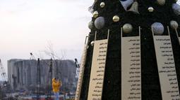 Daftar nama korban yang tewas dalam insiden ledakan di Pelabuhan Beirut menghiasi pohon Natal di dekat silo gandum yang rusak di Beirut, Lebanon (22/12/2020). Ledakan tersebut menewaskan sedikitnya 190 orang dan melukai sekitar 6.000 orang lainnya. (Xinhua/Bilal Jawich)