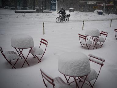 Seorang pria pengantar makanan melewati meja makan yang tertutup salju di tengah kota saat badai salju melanda New York, Senin, (1/2/2021). Badai salju menyebabkan timbunan salju setinggi satu kaki di sepanjang wilayah pesisir timur Amerika Serikat, termasuk Kota New York. (AP Photo/Wong Maye-E)