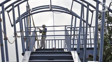 Pekerja menyelesaikan pembangunan jembatan penyeberangan orang (JPO) di dekat Stasiun Jatinegara, Jakarta, Senin (11/5/2020). JPO yang ditargetkan rampung pada tahun ini tersebut sekaligus menjadi jalur keluar penumpang kereta Stasiun Jatinegara. (merdeka.com/Iqbal S. Nugroho)