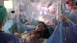 Musisi Dagmar Turner bermain biola saat operasi pengangkatan tumor otak di King's College Hospital, London, 31 Januari 2020. Turner terus memainkan biola saat pengangkatan tumor dari lobus frontal bagian kanan, dekat dengan bagian yang mengontrol gerakan tangan kirinya (KING'S COLLEGE HOSPITAL/AFP)