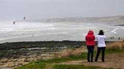 Dua wanita melihat peselancar layang selama cuaca badai di Teluk Wissant, Prancis utara (9/2/2020). Badai Ciara melanda sejumlah wilayah di Inggris dan benua Eropa bagian utara dengan hujan lebat disertai angin kencang pada Minggu 9 Februari 2020. (AFP Photo/Denis Charlet)