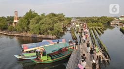 Wisatawan usai menaiki perahu saat mengunjungi Taman Wisata Hutan Bakau (Mangrove) di Desa Segarajaya, Tarumajaya, Bekasi, Jawa Barat (24/11/2019). Taman wisata hutan bakau ini menjadi salah satu destinasi favorit warga, baik dari dalam maupun luar Bekasi. (merdeka.com/Iqbal S. Nugroho)