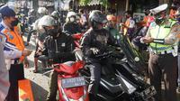 Aparat gabungan dari Polrestabes Bandung, TNI, Satpol PP, dan Dinas Perhubungan, memperketat pemeriksaan kendaraan di pintu masuk Kota Bandung tepatnya Bundaran Cibiru, untuk mencegah penyebaran virus Corona (Covid-19). (Liputan6.com/Huyogo Simbolon)
