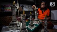 Sugito (68) menyelesaikan pembuatan miniatur Monas dari kertas koran bekas di Bank Sampah Tri Alam Lestari, Pesanggrahan, Jakarta Selatan, Rabu (9/6/2021). Pengolahan Kertas bekas itu dikumpulkan melalui bank sampah yang dikelola putrinya. (Liputan6.com/Johan Tallo)