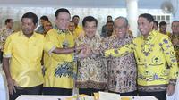 Wapres Jusuf Kalla (tengah) bersama Ketum Partai Golkar versi munas Bali Aburizal Bakrie, Ketum Partai Golkar versi munas Ancol Agung Laksono berjabat tangan setelah penandatanganan kesepakatan islah di Jakarta, Sabtu (30/5). (Liputan6.com/Johan Tallo)