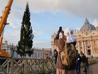 Biarawati mengambil foto saat sebuah derek dikerahkan untuk mendirikan pohon Natal raksasa di Lapangan Santo Petrus, Vatikan, Kamis (22/11). Pohon cemara yang didatangkan dari Hutan Consiglio di Italia ini tingginya mencapai 23 meter (AP/Andrew Medichini)