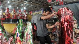 Pedagang parcel merapihkan barang dagangannya di kawasa Cikini, Jakarta, Jumat (16/12). Jelang hari raya Natal, penjualan parcel di kawasan Cikini masih sepi pemebeli. (Liputan6.com/Yoppy Renato)
