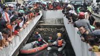 Warga dan pengendara berkerumun melihat upaya tim gabungan melakukan pencarian buaya di Kali Grogol, Jakarta Barat, Kamis (28/6). Pencarian telah dilakukan sejak kemarin siang ketika warga melaporkan penampakan buaya itu. (Merdeka.com/Iqbal S. Nugroho)