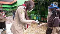 Guru memeriksa suhu tubuh siswa saat hari pertama uji coba Pembelajaran Tatap Muka (PTM) di SDN Kenari 08 Pagi, Jakarta, Rabu (7/4/2021). Pemprov DKI Jakarta mulai melakukan uji coba pembelajaran tatap muka secara terbatas di 100 sekolah mulai 7 hingga 29 April 2021. (Liputan6.com/Faizal Fanani)