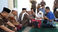 Kepala BPBD Sampang, Anang Djoenaidi saat prosesi mengucap dua kalimat syahadat dibimbing langsung Rois Syuriah PCNU Sampang KH Syafiuddin Abdul Wahid. (liputan6.com/Musthofa Aldo)