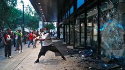 Pengunjuk rasa menghancurkan jendela di kantor pusat CNN di Atlanta, Georgia, Jumat (29/5/2020). Massa yang mengecam kematian George Floyd (46) oleh polisi melakukan vandalisme dan perusakan gedung CNN pusat. (Alyssa Pointer/Atlanta Journal-Constitution via AP)