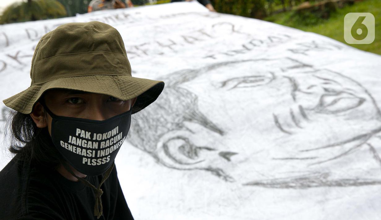 Sejumlah aktivis melakukan aksi simbolik di kawasan Patung Kuda, Jakarta, Kamis (18/3/2021). Aktivis menuntut Presiden Joko Widodo untuk mencabut Omnibus Law UU Cipta Kerja dan regulasi turunannya yang menghapus Fly Ash Bottom Ash (FABA) dari daftar limbah B3. (Liputan6.com/Faizal Fanani)