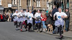 Amy Butler berlari memimpin lomba lari dengan membawa pancake dalam lomba tahunan Pancake Trans-Atlantic di kota Olney, Buckinghamshire, Inggris, Selasa (5/3). Peserta juga harus membolak-balikan pancake sambil tetap berlari. (AP/Frank Augstein)