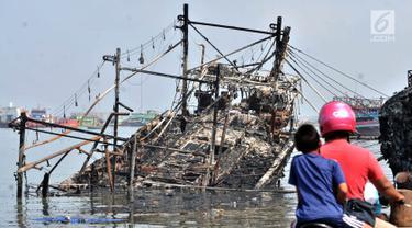 Pengendara sepeda motor melintas dekat kapal yang ludes dilalap api di Pelabuhan Muara Baru, Jakarta, Minggu (24/2). Sebanyak 18 unit kapal tradisional hangus akibat kebakaran pada Sabtu, 23 Februari 2019. (Merdeka.com/Iqbal Nugroho)