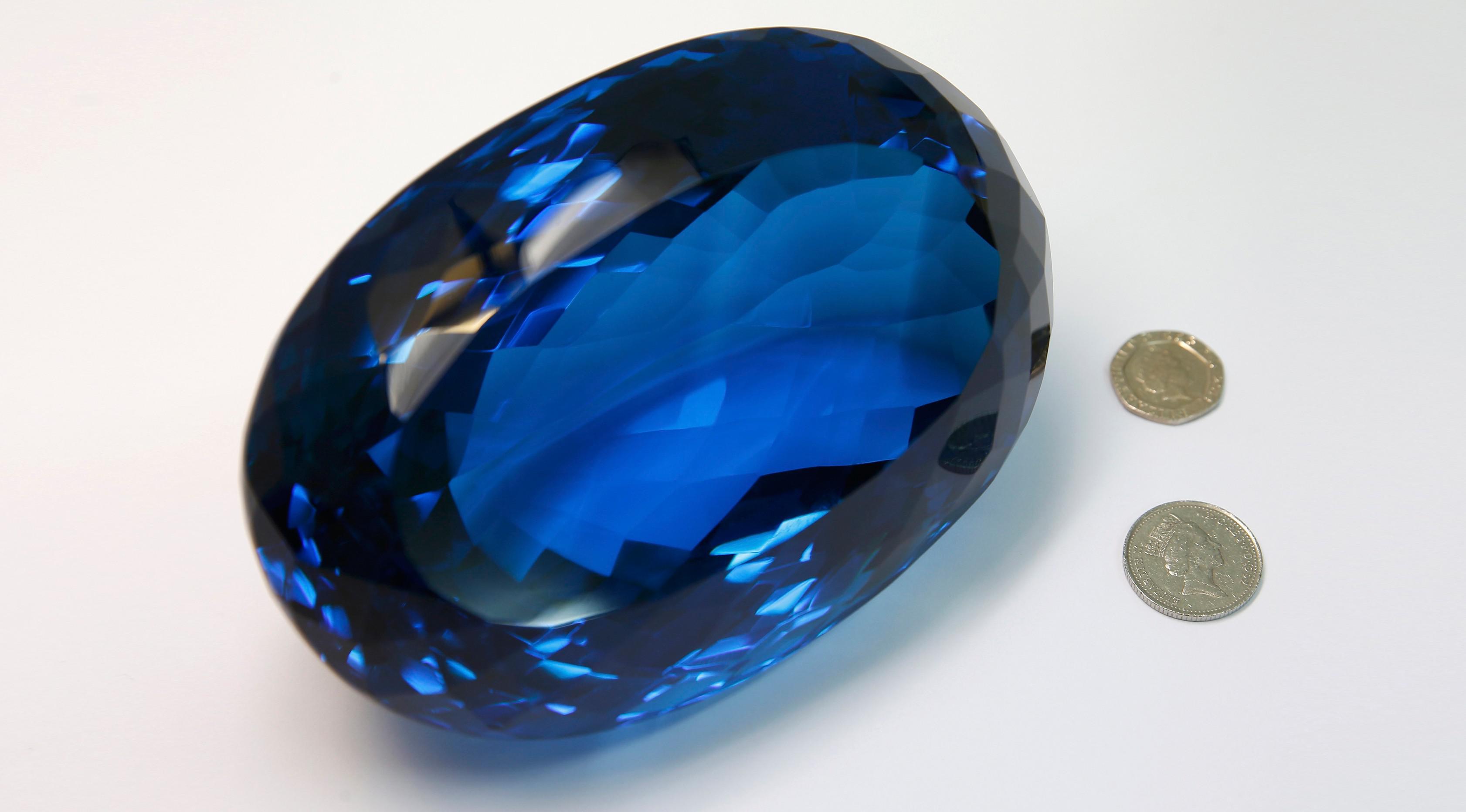 Batu permata jenis topaz berwarna biru disandingkan dengan uang koin di Museum Sejarah Alam London, Inggris, Selasa (27/9). Batu milik Maurice Ostro ini menjadi batu topaz terbesar di dunia. (REUTERS / Peter Nicholls)