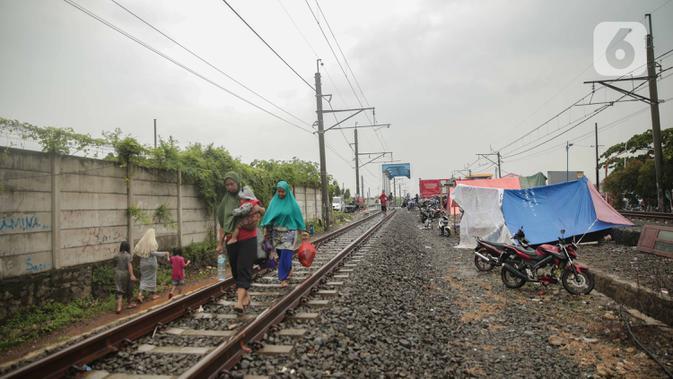 Tenda pengungsi banjir didirikan di jalur rel kereta commuterline Tangerang-Duri di Kembangan Baru, Jakarta, Jumat (3/1/2020). Jalur rel yang nonaktif sementara karena banjir dimanfaatkan warga sekitar untuk mendirikan tenda darurat karena rumah mereka masih terendam. (Liputan6.com/Faizal Fanani)