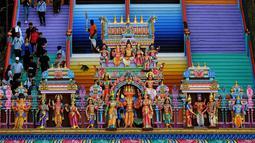 Pengunjung menaiki tangga 272 langkah yang baru dicat, jalan untuk menuju kuil Batu Caves di Kuala Lumpur, 30 Agustus 2018. Pengelola disebut tak mendapat izin dari Kementerian Kebudayaan Malaysia sebelum melakukan renovasi tersebut (AFP/Manan VATSYAYANA)