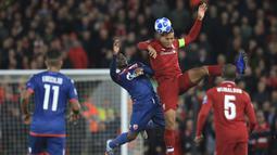 Bek Liverpool, Virgil Van Dijk, duel udara dengan dengan pemain Crvena Zvezda, El Fardou Ben Nabouhane, pada laga Liga Champions, di Stadion Anfield, Rabu (24/10/2018). Liverpool menang 4-0 atas Crvena Zvezda. (AP/Jon Super)
