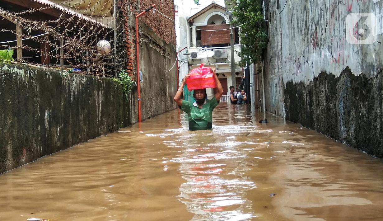 Warga berjalan menyusuri banjir yang merendam permukiman di kawasan Kebalen, Jakarta, Sabtu (20/2/2021). Curah hujan yang tinggi menyebabkan banjir setinggi orang dewasa di kawasan Kebalen. (Liputan6.com/Johan Tallo)