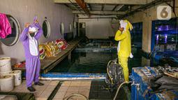 Penyelam dengan kostum kelici bersiap sebelum tampil dalam pertunjukan Rabbit Underwater Show In Mission Save The Ocean di Sea World Ancol Jakarta, Selasa (30/3/2021). Pertunjukan digelar untuk mengedukasi warga dalam menjaga ekosistem laut dari sampah atau polusi laut. (Liputan6.com/Faizal Fanani)