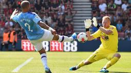 Kiper Bournemouth, Aaron Ramsdale, berusaha menahan bola tendangan Bek Manchester City, Kyle Walker, pada laga Premier League 2019 di Stadion Vitality, Minggu (25/8). Manchester City menang 3-1 atas Bournemouth. (AFP/Glyn Kirk)