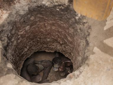 Dua buruh tambang saat mencari batu safir di dalam lubang tanah yang digali di kawasan pertambangan batu safir di Sakaraha, Madagaskar. Batu Safir pertama kali ditemukan di Madagaskar pada akhir 1990-an. (AFP Photo/Gianluigi Guercia)