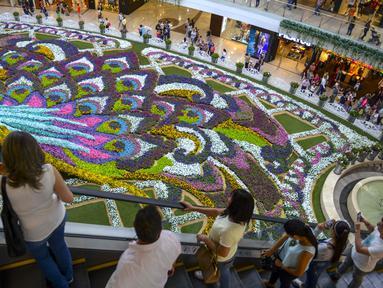 Sejumlah pengunjung melihat merak raksasa selama Festival Bunga di Pusat Perbelanjaan Santa Fe di Medellin, Kolombia (3/8). Merak yang terbuat dari 182.000 bunga ini memiliki panjang 12 meter (40 kaki). (AFP Photo/Joaquin Sarmiento)