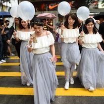 Sekelompok perempuan mengenakan gaun untuk menghadiri pernikahan menyeberangi jalan di tengah demo menentang undang-undang keadaan darurat, di Hong Kong, 12 Oktober 2019. (Source: AFP)