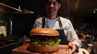 Chef dari restoran The Oak Door, Patrick Shimada berpose dengan burger raksasa di hotel Grand Hyatt Tokyo, Senin (1/4). Golden Giant Burger dibuat untuk memperingati penobatan Putra Mahkota Naruhito pada 1 Mei 2019 dan menandai awal era 'Reiwa' bagi Jepang. (CHARLY TRIBALLEAU/AFP)