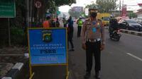 Petugas gabungan di Bekasi memantau kendaraan jelang PSBB. (Bam Sinulingga/Liputan6.com)