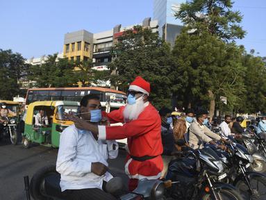 Pengguna jalan dipakaikan masker oleh presiden Angel Foundation dan pekerja sosial, Rufas Christian yang berpakaian Sinterklas di persimpangan lalu lintas di Ahmedabad, India, Kamis (17/12/2020). Aksi itu sebagai bagian dari kampanye kesadaran melawan penyebaran COVID-19. (SAM PANTHAKY/AFP)