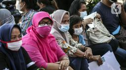 Warga menunggu untuk menerima bantuan sosial (bansos) di kawasan Kedoya Selatan, Jakarta Barat, Rabu (28/7/2021). Bansos ini merupakan alokasi dana yang bersumber dari APBD DKI Jakarta dan menyasar 1.700.379 orang. (Liputan6.com/Johan Tallo)