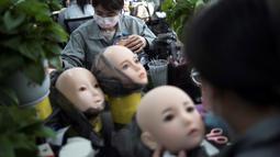 Para pekerja melukis wajah boneka seks di pabrik EXDOLL, sebuah perusahaan yang terletak di Dalian, China, Kamis (1/2). Selain bisa berbicara, boneka seks ini juga bisa bermain musik dan menyalakan mesin pencuci piring. (AFP PHOTO/FRED DUFOUR)