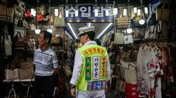Seorang pria mengenakan rompi saat mengiklankan pakaian, sepatu, dan tas di luar sebuah toko di pasar Namdaemun di Seoul (2/7/2019). Dibangun pada tahun 1946, Pasar Namdaemun merupakan salah satu pasar tradisional yang terbesar di Korea. (AFP Photo/Minji Suh)