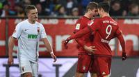 Robert Lewandowski dan Thomas Muller merayakan gol Bayern Munchen ke gawang Augsburg pada laga Bundesliga di WWK Arena, Augsburg, Minggu (14/2/2016) malam WIB. (AFP/Christoph Stache)