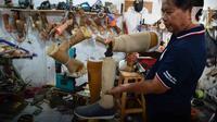 Perajin membuat kaki dan tangan palsu di Kawasan Tangerang, Kamis (2/7/2020). Menko Bidang Perekonomian Airlangga Hartarto menyebutkan penerapan new normal berpengaruh pada peningkatan signifikan penyaluran Kredit Usaha Rakyat (KUR) yang terjadi di pekan kedua Juni 2020. (Liputan6.com/Angga Yuniar)