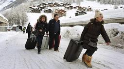 Sejumlah turis menuju heliport untuk dievakuasi dari Zermatt di Swiss (10/1). Pemadaman listrik di beberapa daerah lain, seperti di Kota Valais, juga terjadi akibat hujan salju lebat. (AFP Photo/Mark Ralston)