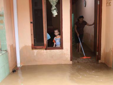 Warga membersihkan rumah mereka akibat banjir yang melanda Kampung Melayu, Jakarta Timur, Senin (25/6). Ketinggian air di Sungai Ciliwung meningkat sehingga merendam sejumlah wilayah di Jakarta. (Liputan6.com/Arya Manggala)